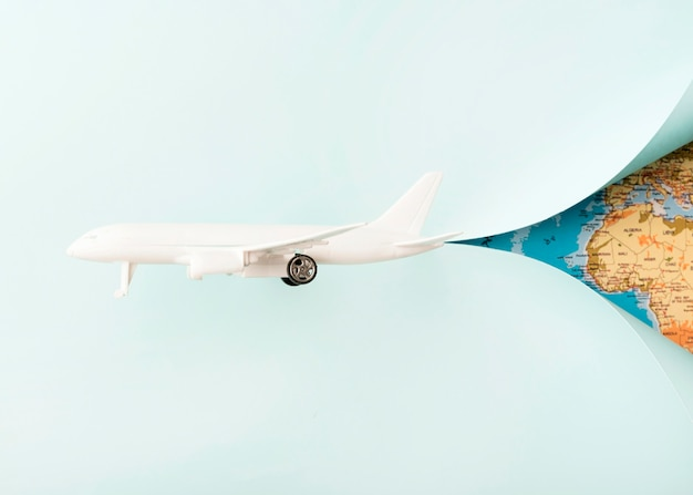 Avião de brinquedo branco com mapa mundial