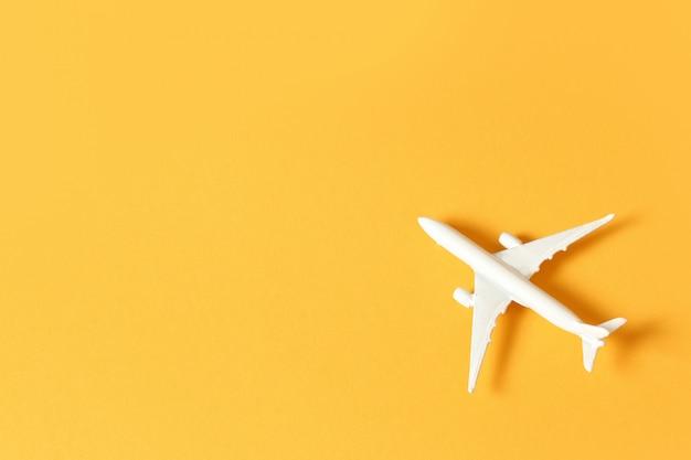 Avião de brinquedo branco sobre um fundo amarelo com espaço de cópia