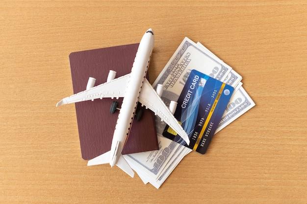 Avião de brinquedo, cartões de crédito, dólares e passaporte na mesa de madeira. conceito de viagens