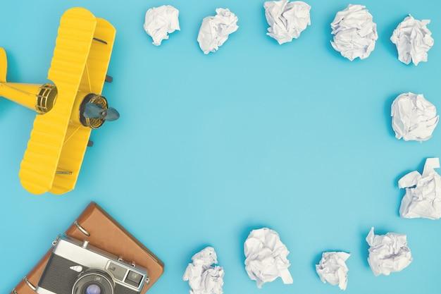 Avião de brinquedo com nuvem de papel no espaço cópia azul para o conceito de viagens