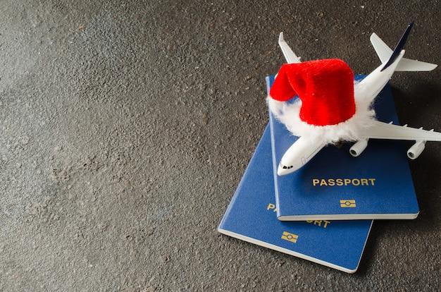 Avião de brinquedo com passaporte e chapéu de papai noel.