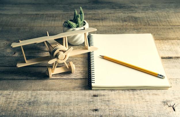 Avião de brinquedo de madeira com caderno em branco e lápis na mesa de madeira.