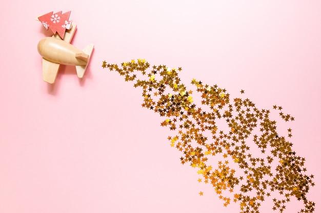 Avião de brinquedo de madeira com confetes dourados sobre uma superfície rosa