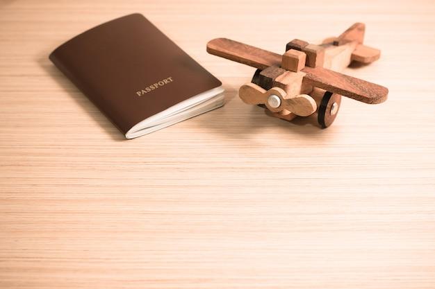 Avião de brinquedo de madeira e o passaporte com espaço de cópia. conceito de viagens