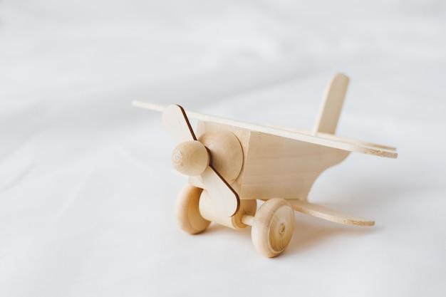 Avião de brinquedo de madeira fica em um fundo branco
