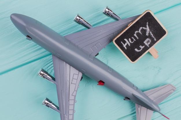 Avião de brinquedo e placa de identificação nele. extremo close-up. fundo azul da superfície da mesa de madeira.
