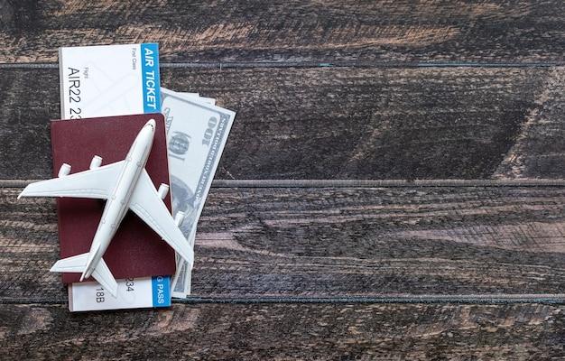 Avião de brinquedo em cima de dólares e um passaporte em uma superfície de madeira
