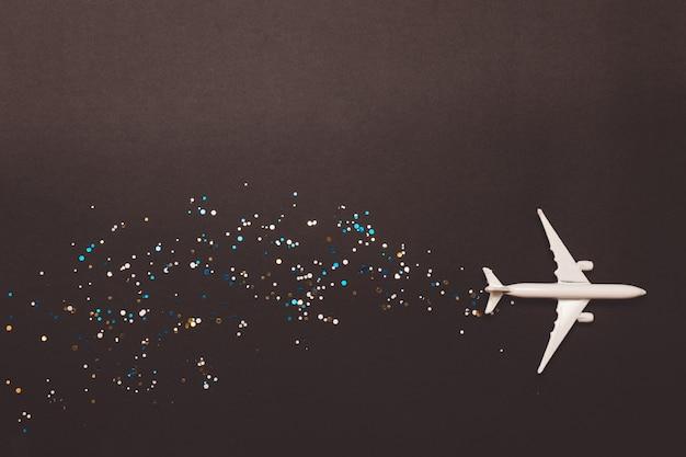 Avião de brinquedo em miniatura com brilhos em fundo amarelo. viagem