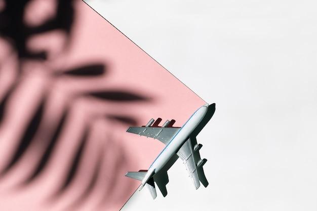 Avião de brinquedo em um fundo branco e rosa com uma sombra de uma palmeira.