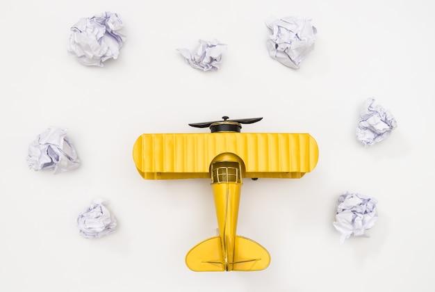 Avião de brinquedo na nuvem de papel na vista superior de fundo branco