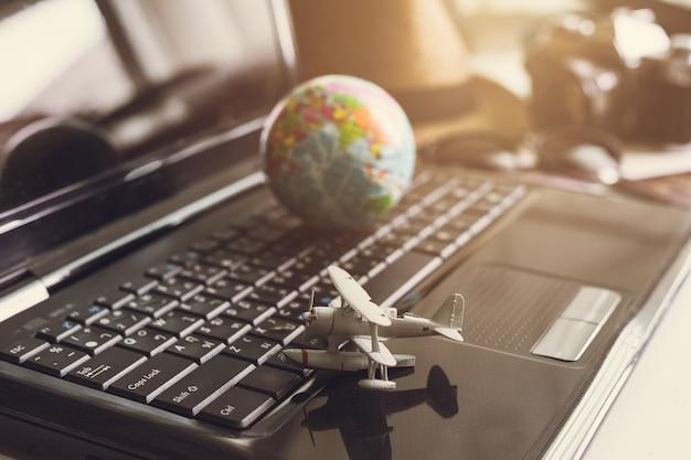 Avião de brinquedo no teclado do laptop com globo e câmera
