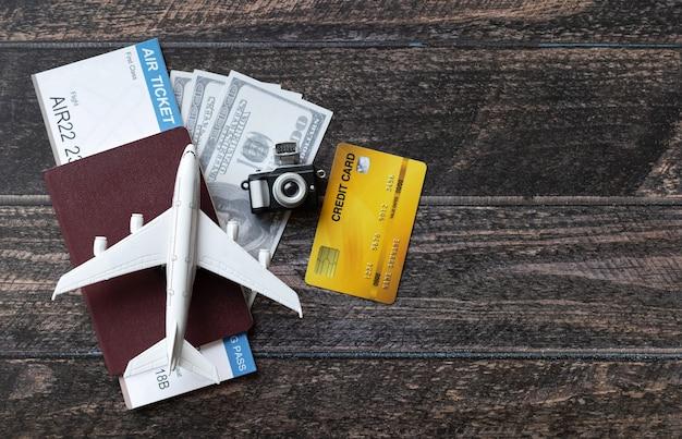 Avião de brinquedo, passagem aérea, cartões de crédito, dólares e passaporte na mesa de madeira. conceito de viagens