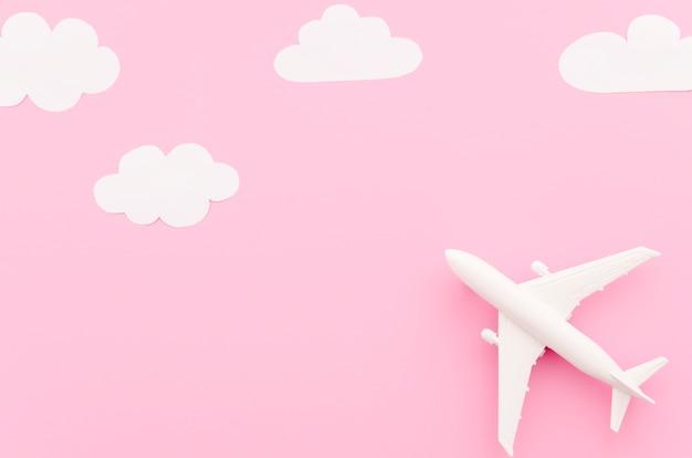 Avião de brinquedo pequeno com nuvens de papel