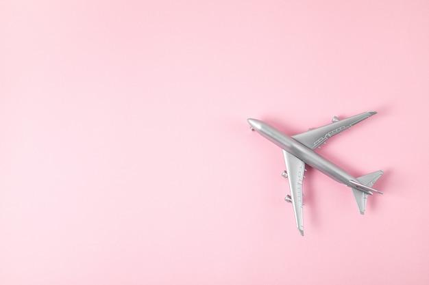 Avião de brinquedo prata sobre fundo rosa