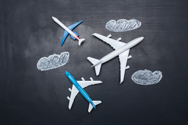 Avião de brinquedo sobre desenhos de lousa e setas