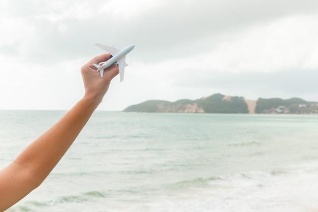 Avião de brinquedo voando, mostrando a praia e o céu, representando viagens e turismo