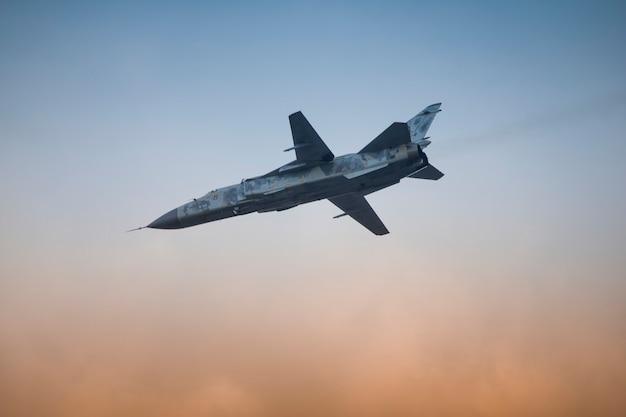 Avião de combate militar com asa de varredura variável no fundo do céu.