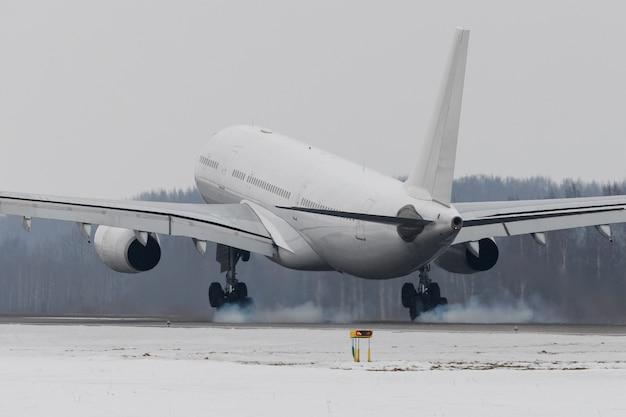 Avião de fuselagem larga pousando na pista com fumaça do chassi, horário de inverno