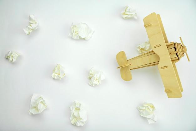 Avião de madeira com bola de papel em vez de nuvens brancas sobre fundo branco papel