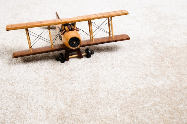 Avião de madeira no tapete