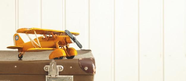Avião de metal amarelo de brinquedo malas retrô velhas fundo de madeira branco vintage tintométrico