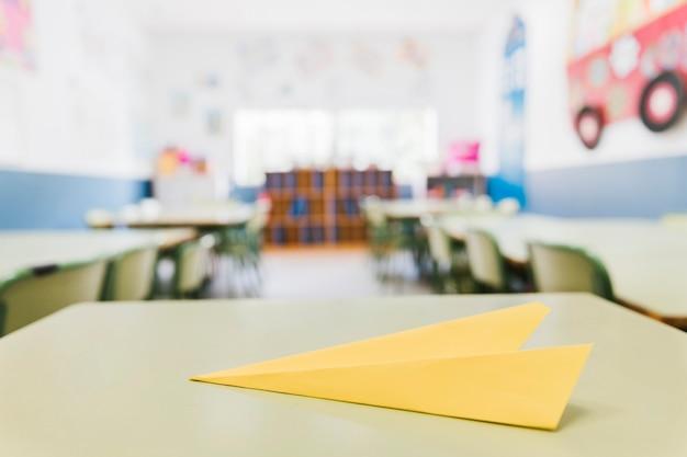 Avião de papel amarelo na mesa na sala de aula