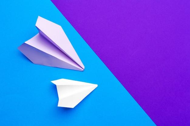 Avião de papel branco em papel azul e roxo