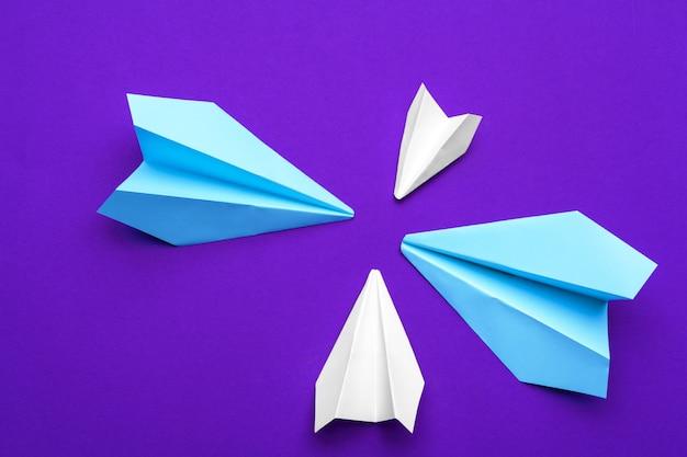 Avião de papel branco em roxo