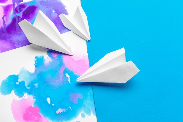 Avião de papel branco em um papel de bloco de cor