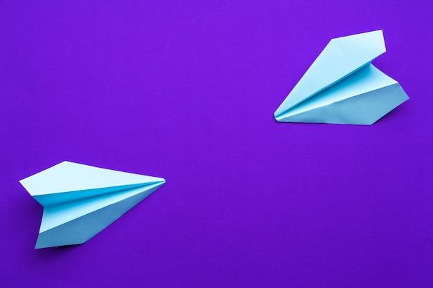 Avião de papel branco em um roxo