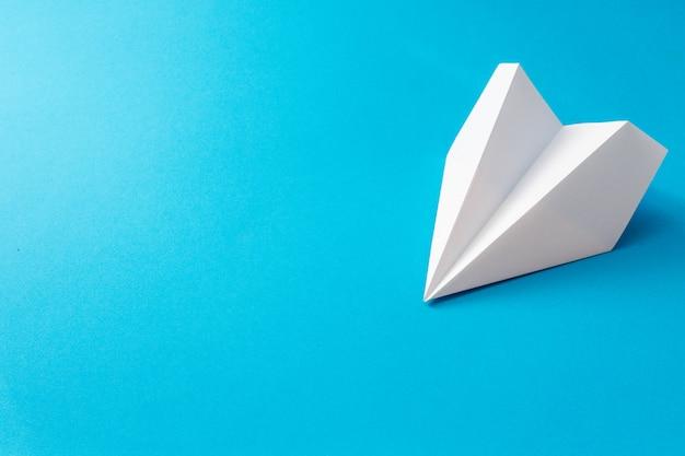 Avião de papel branco sobre fundo azul. ilustração de viagens conceito