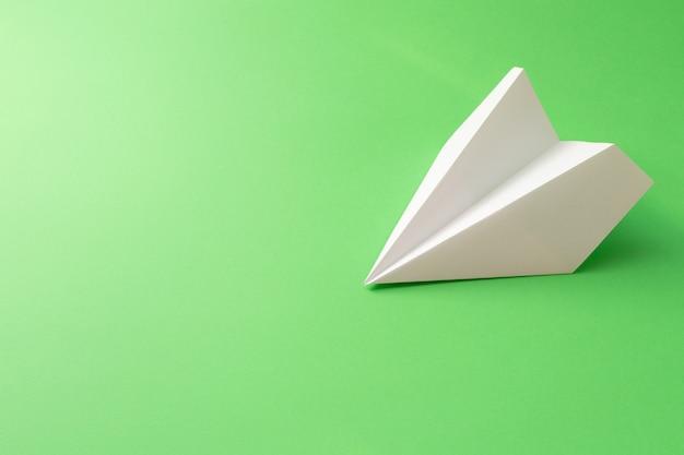 Avião de papel branco sobre fundo verde. ilustração mínima de viagens
