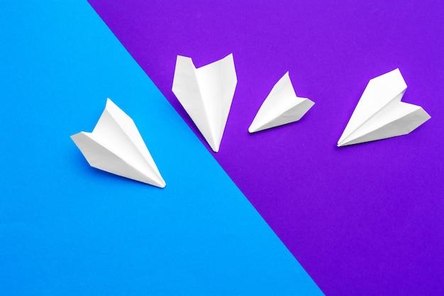 Avião de papel branco sobre um fundo azul e roxo de bloco de cores
