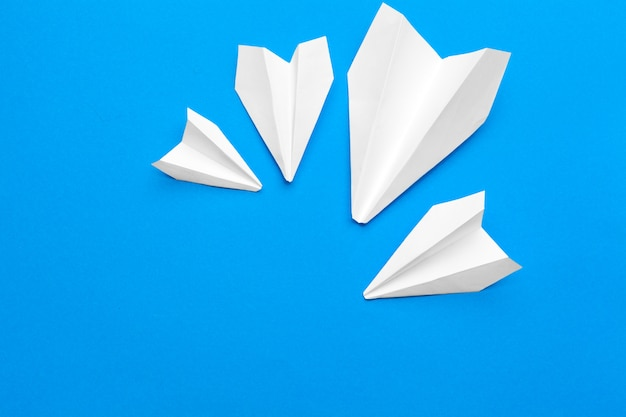 Avião de papel branco sobre um fundo de papel azul