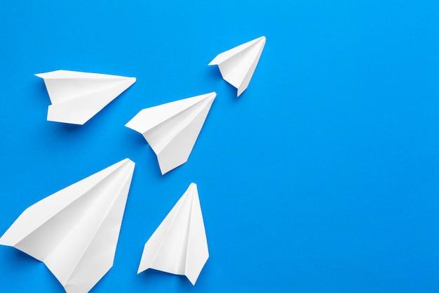 Avião de papel branco sobre um fundo de papel da marinha