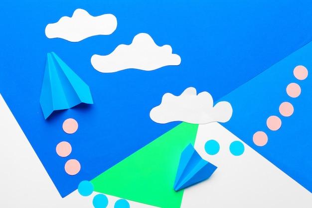 Avião de papel em um azul com nuvens
