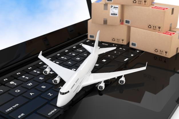 Avião de passageiro de jato branco com caixas de papelão sobre closeup extrema de teclado de computador portátil moderno. renderização 3d.