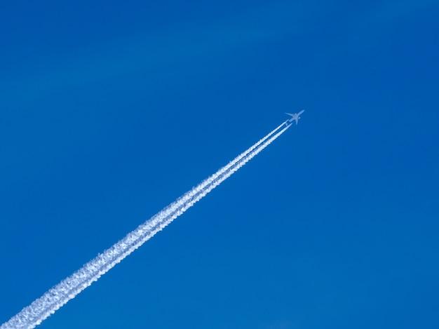 Avião de passageiros a jato branco voando em alta altitude em um céu azul claro e sem nuvens