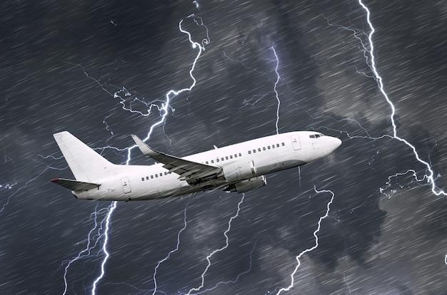 Avião de passageiros branco decola durante uma tempestade noturna com relâmpagos de chuva, mau tempo.