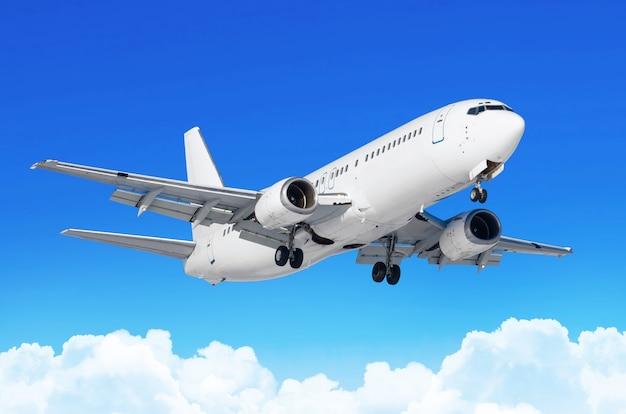 Avião de passageiros com o chassi liberado antes do pouso no aeroporto contra as nuvens cúmulos do céu azul.