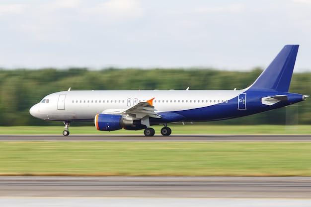 Avião de passageiros de corpo estreito, taxando na pista para decolar, vista lateral, em movimento