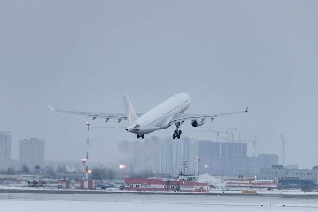Avião de passageiros decola no inverno baixo sobre a pista