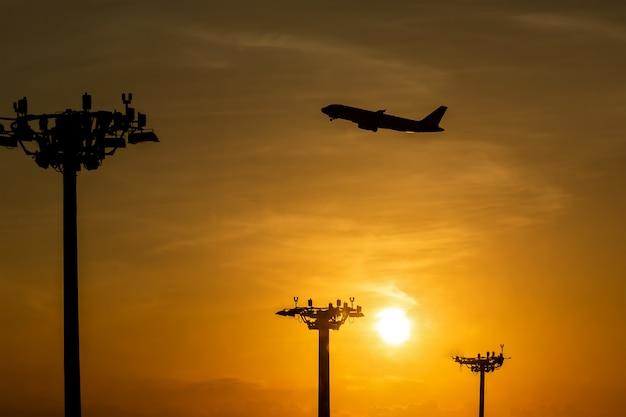 Avião de passageiros está decolando durante um belo nascer do sol. torre de lâmpadas de holofotes nos pilares