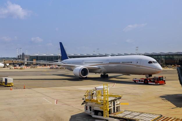 Avião de passageiros na vista do aeroporto com aviões e veículos de serviço perto do terminal de embarque do aeroporto internacional
