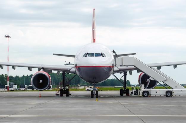 Avião de passageiros no estacionamento no aeroporto com um nariz para a frente e um corredor.