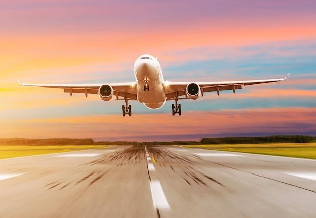 Avião de passageiros pousando ao pôr do sol em uma pista.