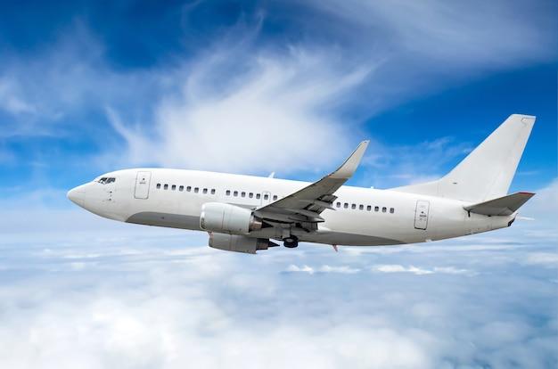Avião de passageiros voa em um nível de vôo contra nuvens e um céu azul.