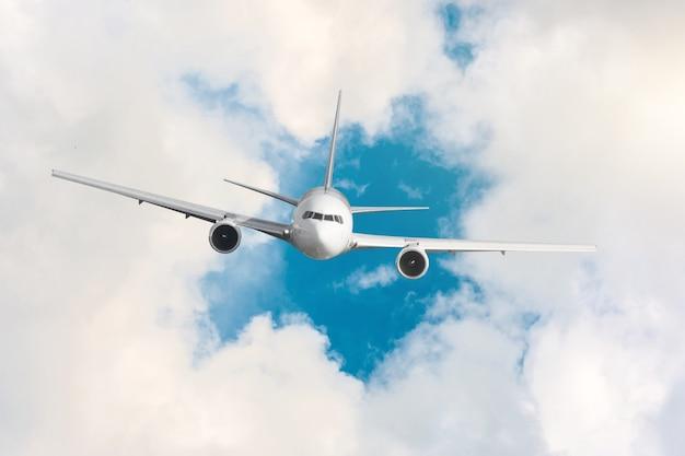 Avião de passageiros voando acima de nuvens e céu azul.
