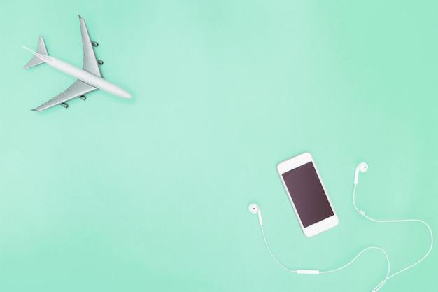 Avião de telefone celular e brinquedo em fundo verde-azulado para o conceito de viagens