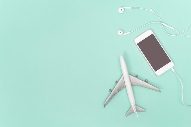 Avião de telefone celular e brinquedo no fundo azul verde-azulado para o conceito de viagens